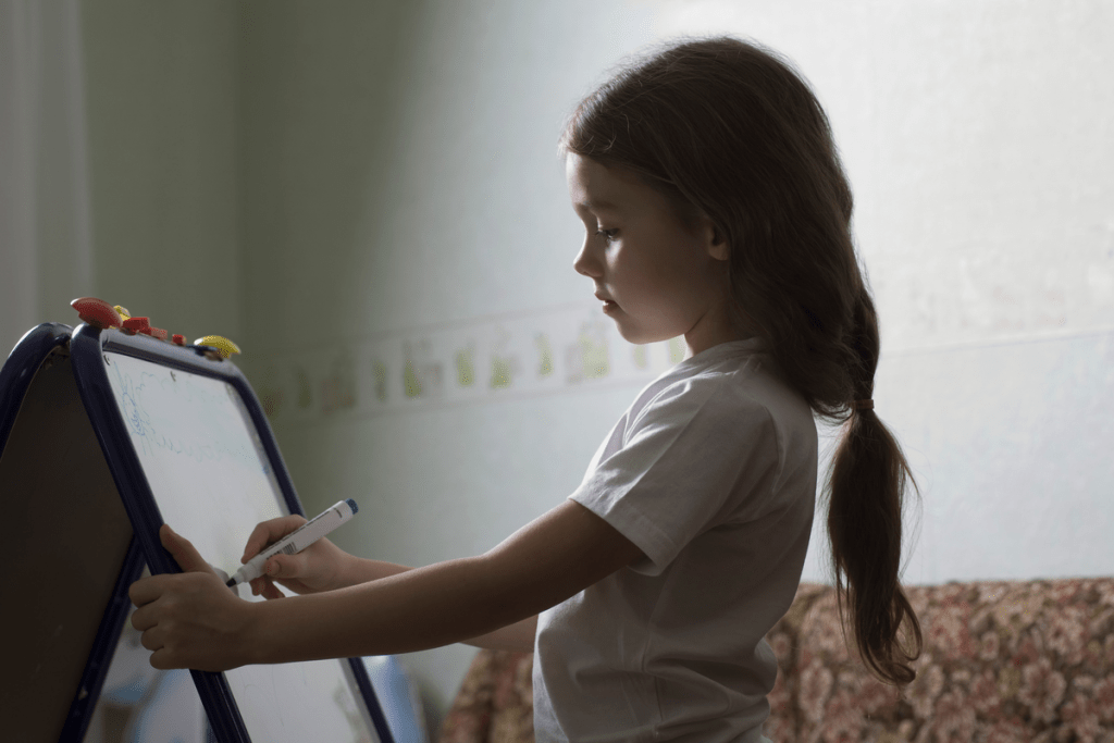 Child standing at easel