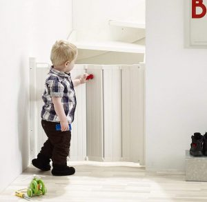 Best retractable baby gates - boy next to a baby gate