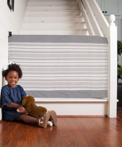 Best retractable baby gates - a girl sitting next to a baby gate