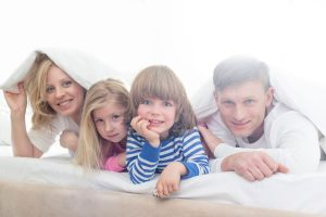 Family in a bed under a blanket