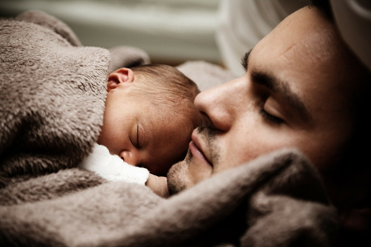 Father with a baby in bed