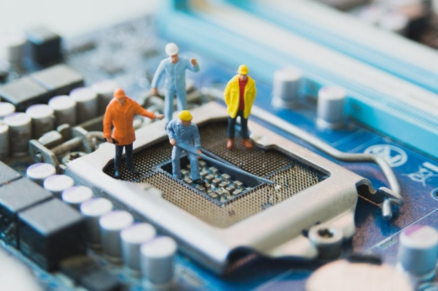 Toy men fixing a microprocessor