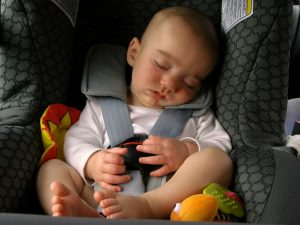 A child sleeping in a car seat for toddlers