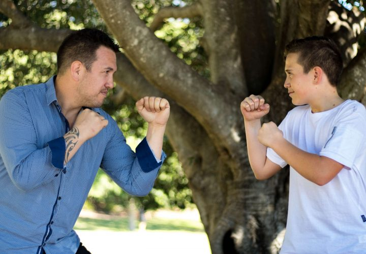 Father play boxing with his teen son