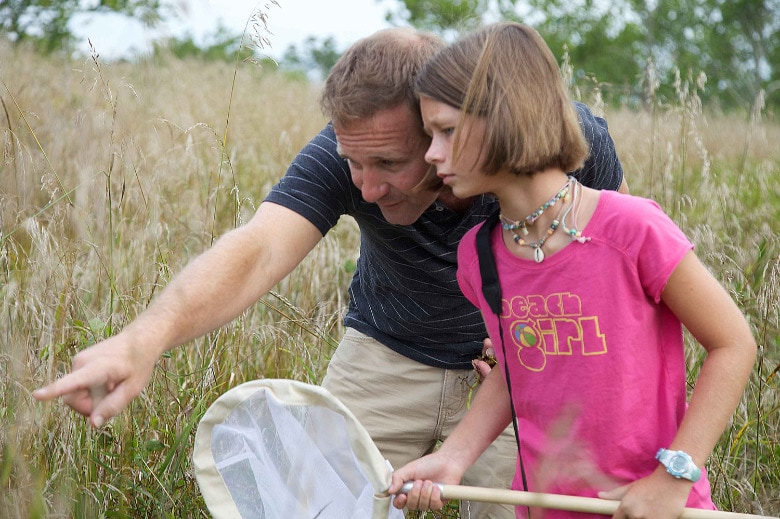 A father catching bugs with his daughter