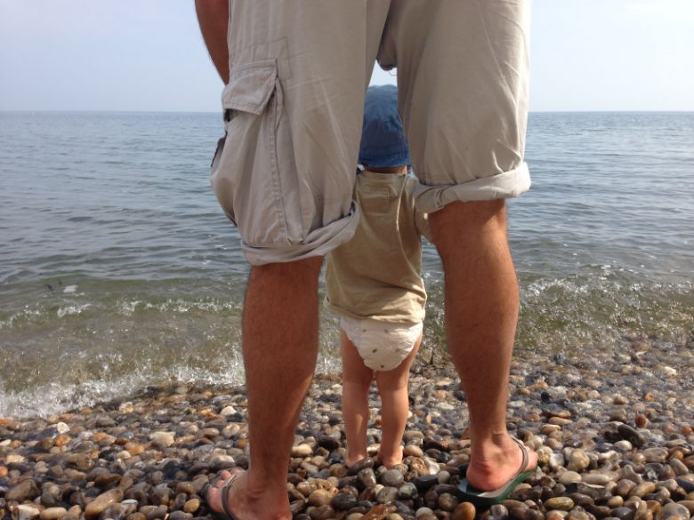 Father holding son at the water's edge