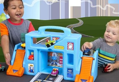 Toddlers playing with a blue and orange toy garage