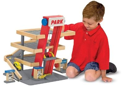 Toddler playing with a wooden garage