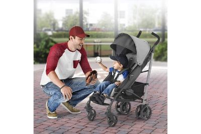 Grey stroller with toddler sitting on it