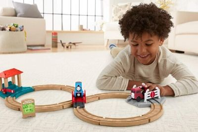 Toddler playing with a wooden train set