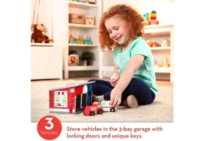 Toddler playing with toy garage and toy ambulance