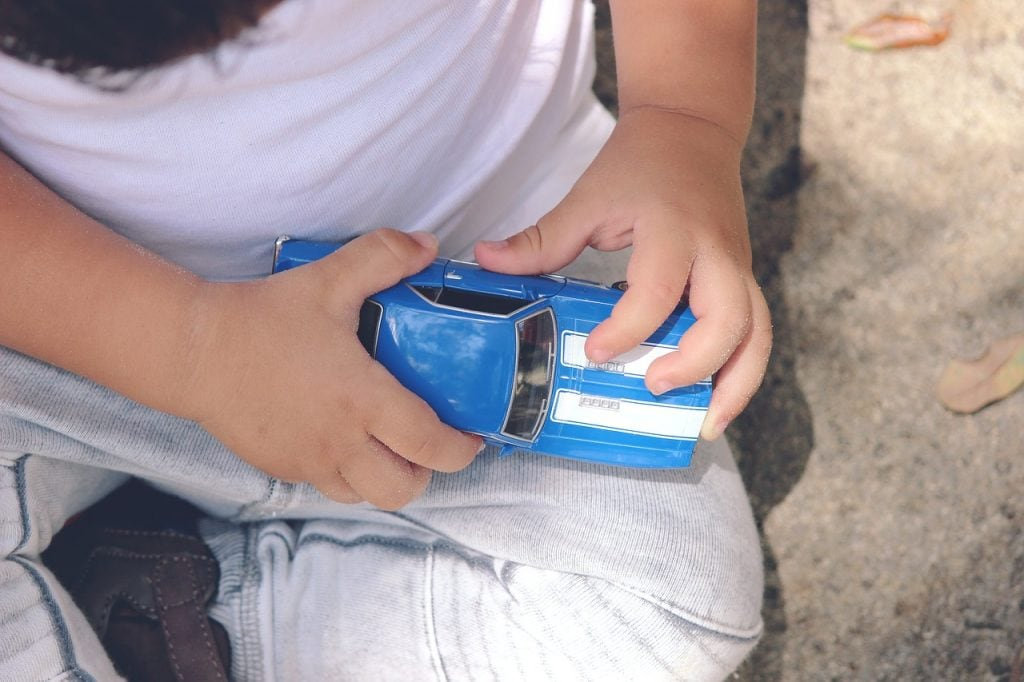 Toddler playing with a blue toy car