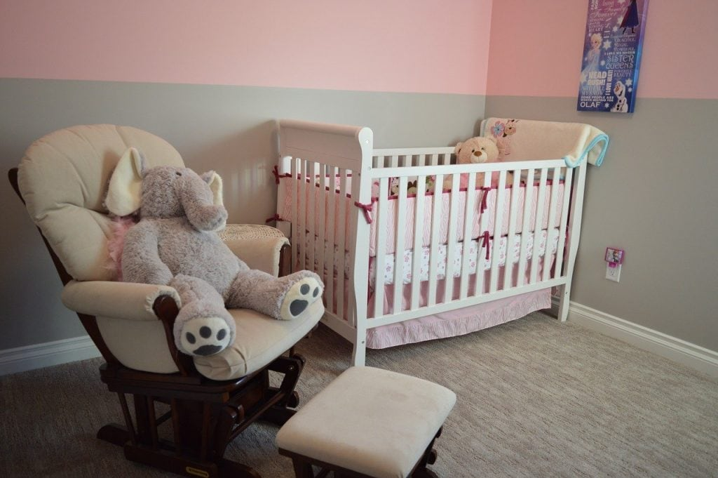 White baby crib in a nursery with elephant and a teddy bear