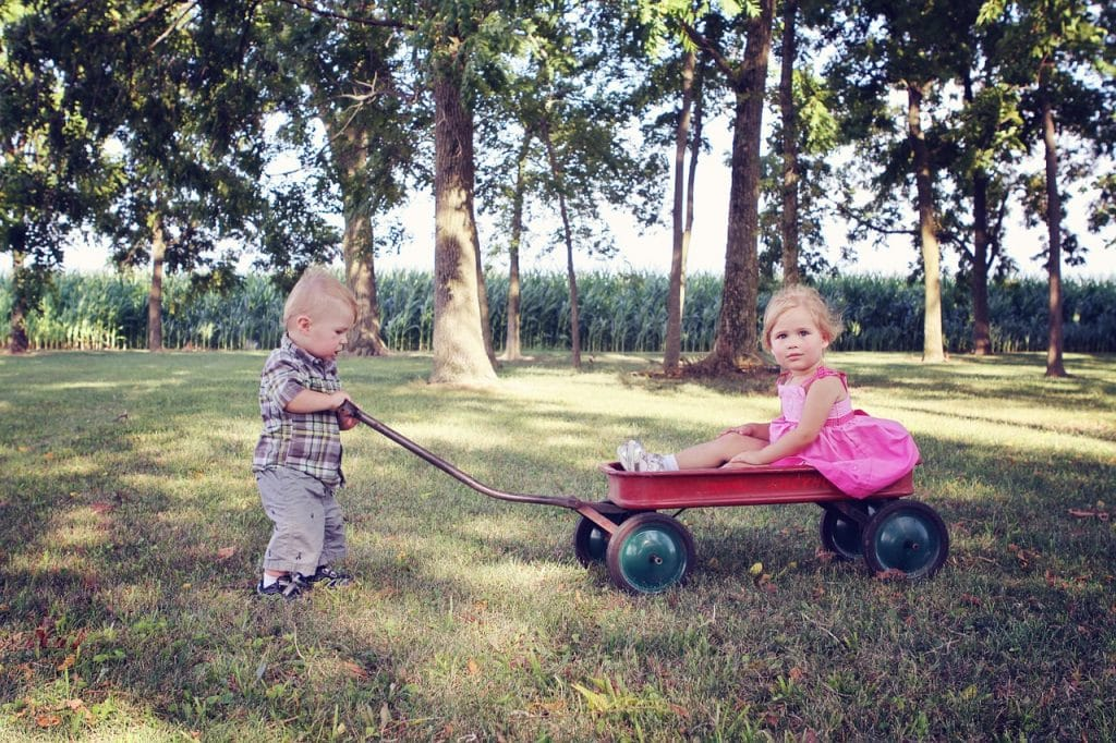 Kids pushing each other on a wagon