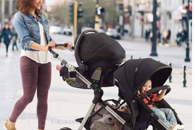 Mother pushing two kids on a travel system