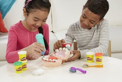 Two kids playing with a mouth set, dentist toys, and play-doh