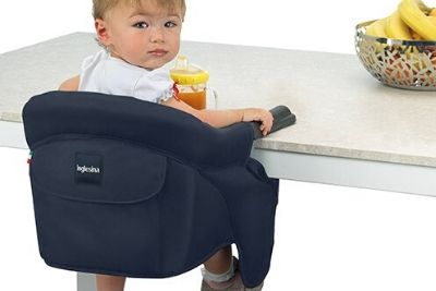 Young toddler sited on a navy blue fast table highchair