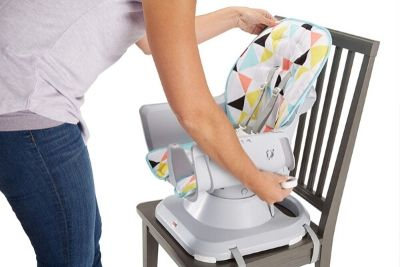 Mom fixing a multi-colored highchair