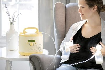 Woman expressing milk using a yellow breast pump
