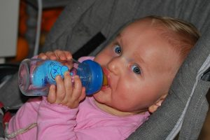 Baby drinking from a blue baby bottle