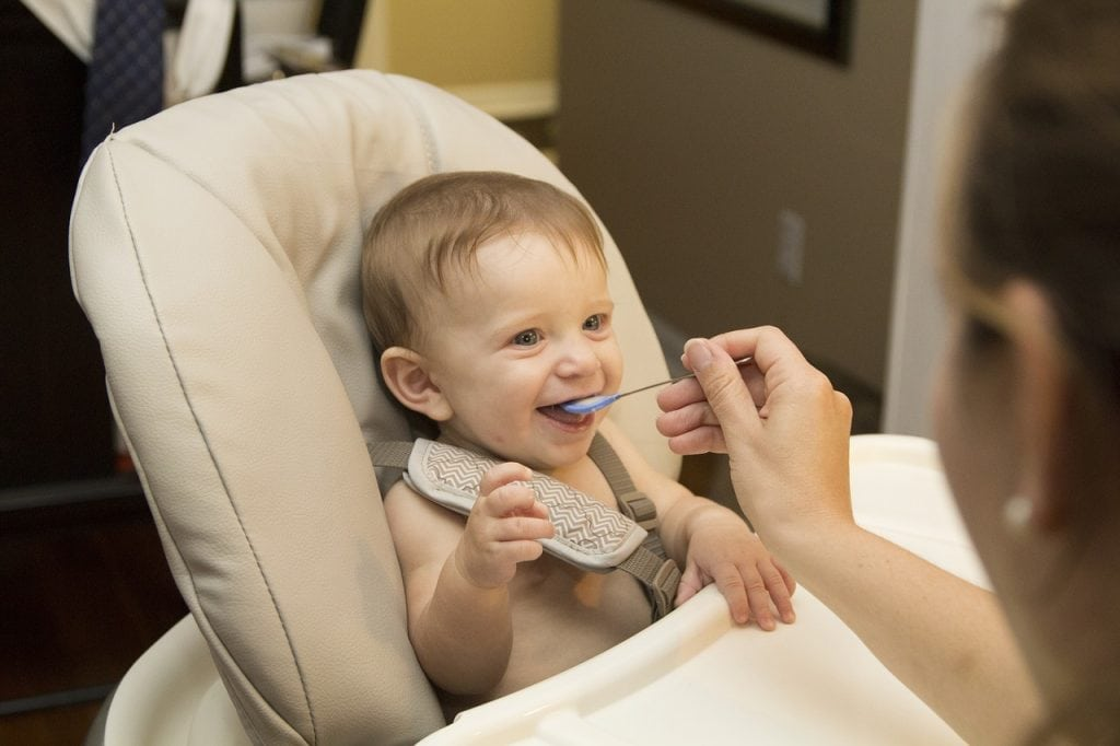 Baby eating food on a high chair