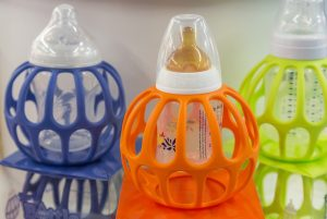 Orange, purple, and green baby bottles