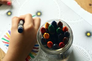 Someone coloring using crayons in a jar