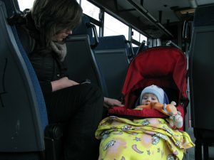 Baby on a stroller traveling with mother on a bus