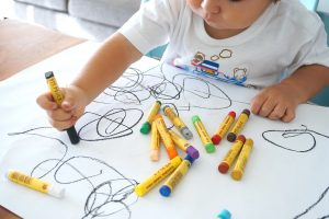 A child using crayons to scribble