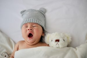 Little baby yawning with teddy bear