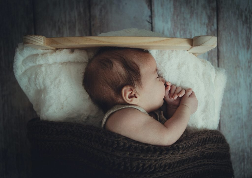 Little baby sleeping in old fashioned baby bed