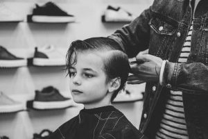 Young boy getting a hair cute