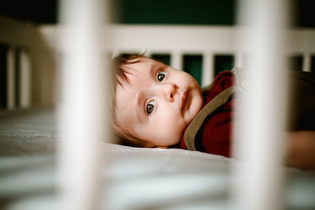 Toddler staring out of crib bars