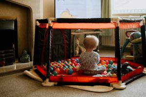 Baby sitting in a play yard - a baby walker alternative