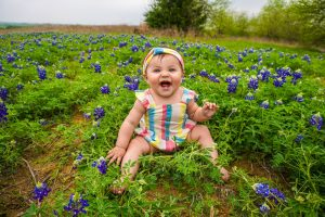 Little girl toddler smiling in a field of flower