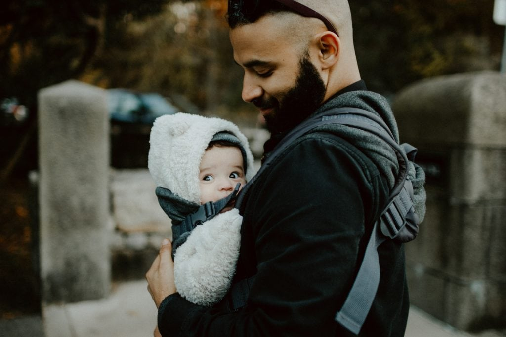 Man holding his baby in a baby carrier