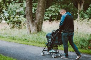 Man pushing child in stroller through park