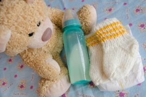 Bottle, baby booties and bear