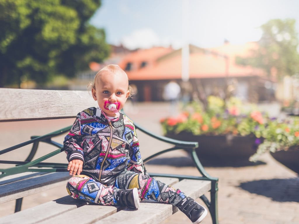 Toddler with pacifier sitting on green bench