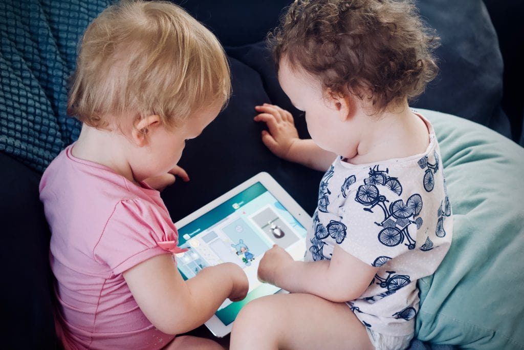 Twins with pink and pattern shirts reading a book