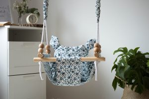 Wooden hanging baby swing with floral patterned seat