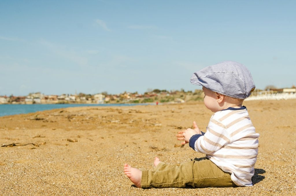 Baby on the beach with a blue hat