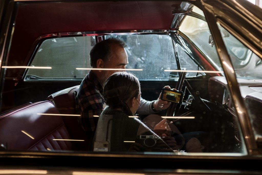Infant in car with man holding camera