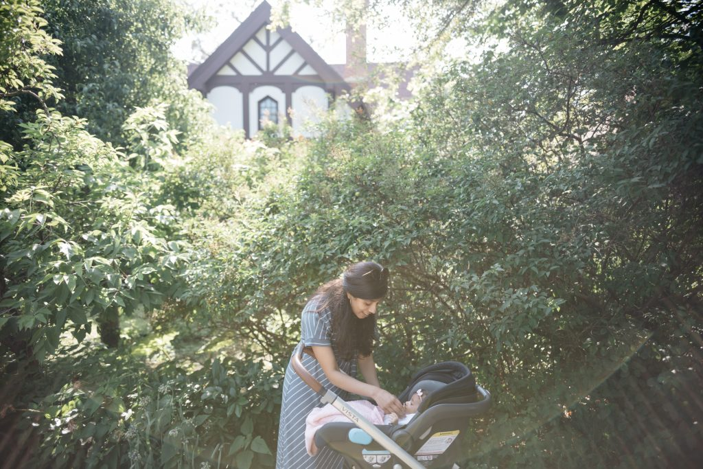 Mother talking to baby in stroller in the garden