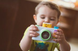 Baby holding a camera toy