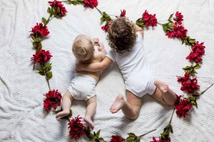 Two babies surrounded with a heart shaped-flower