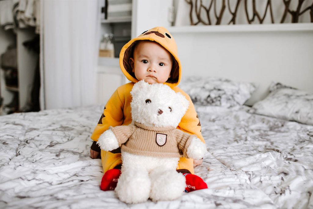 toddler sitting on the bed with his bear