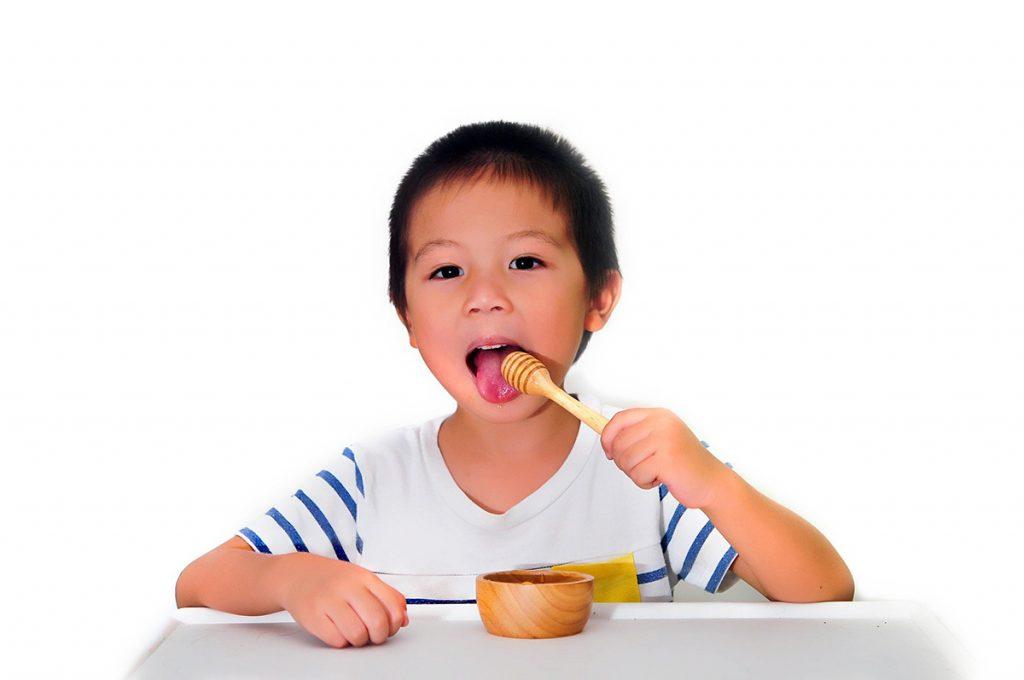 Little boy eating honey