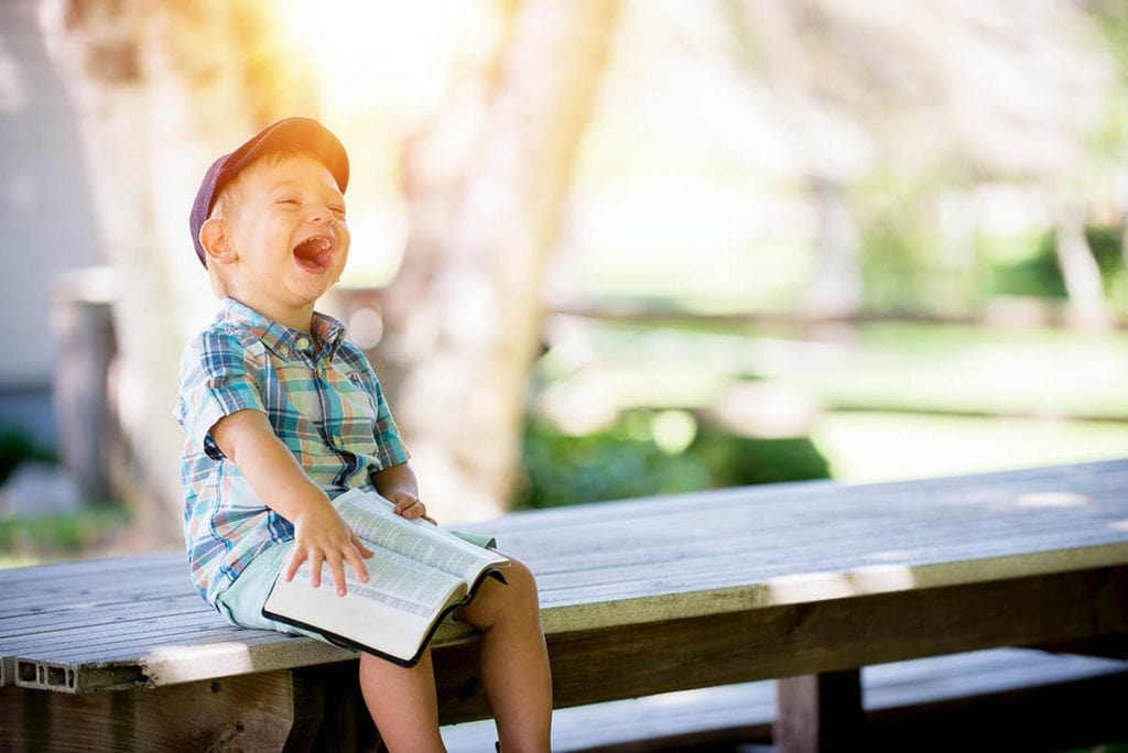 A boy sitting and laughing