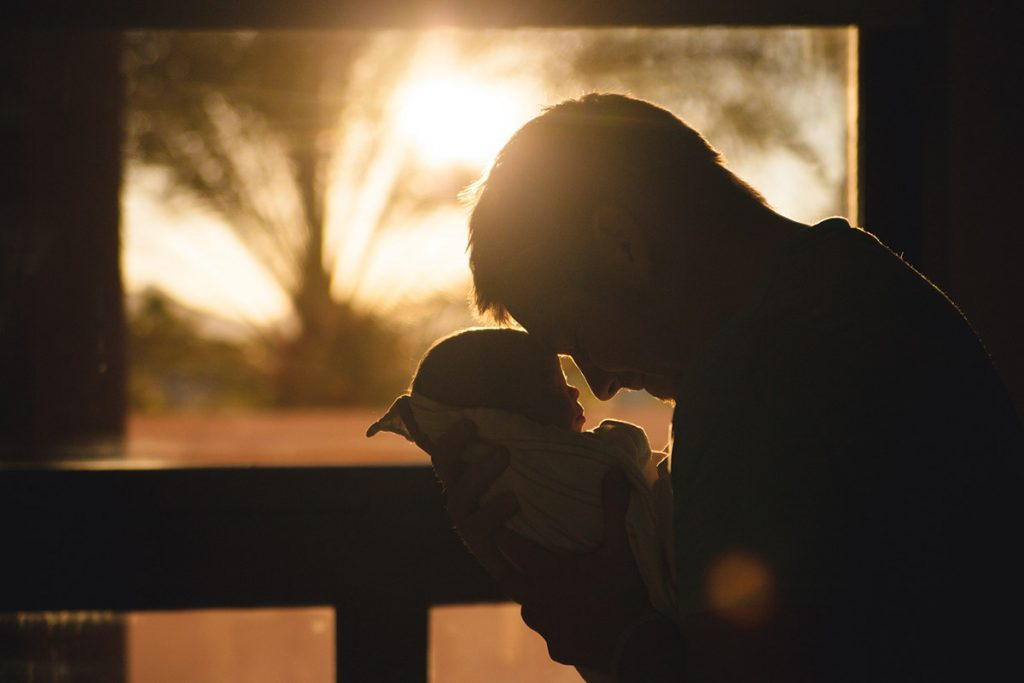 Man carrying his baby in a silhouette